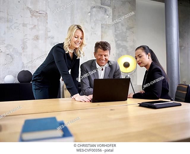 Businessman and two businesswomen sharing laptop in modern office