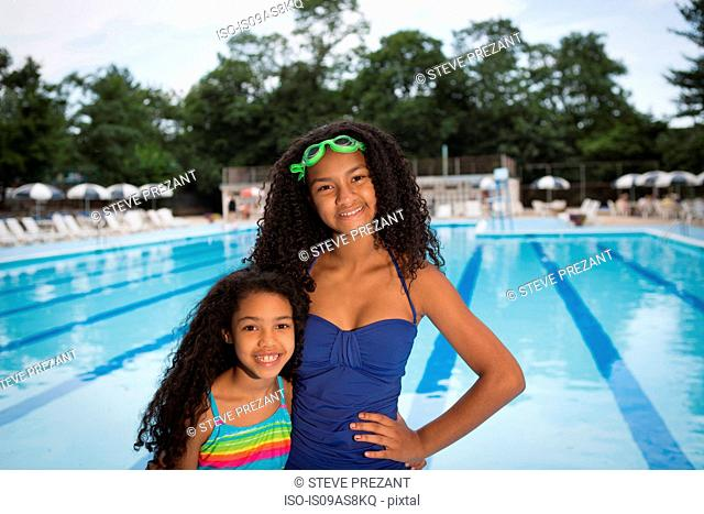 sisters wearing swimsuits standing in front of swimming pool, looking at camera smiling