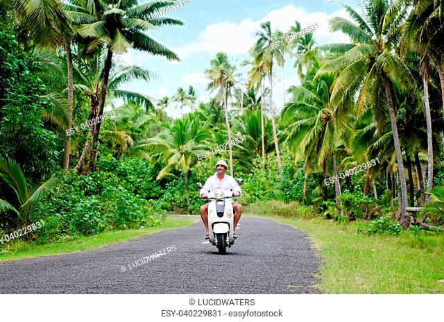 AITUTAKI - SEP 20:Tourist man drives hired motorbike on Sep 20 2013.It's one of the must popular activity in the Island but Cook Islands Driver's License is...