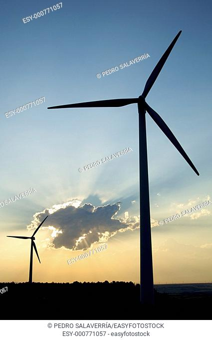 two windmills against cloudy sky at sunset in Tardienta, Huesca, Aragon, Spain