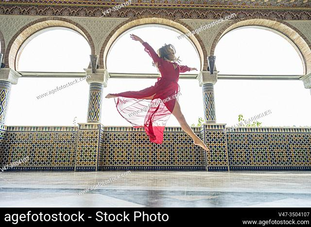 Young woman jumping a large grand jete while dancing, photographed in flight