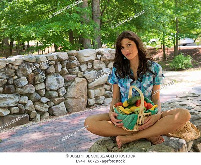 32 year old brunette woman in casual summer dress sitting cross-legged on a stone wall holding a basket of mixed vegetables