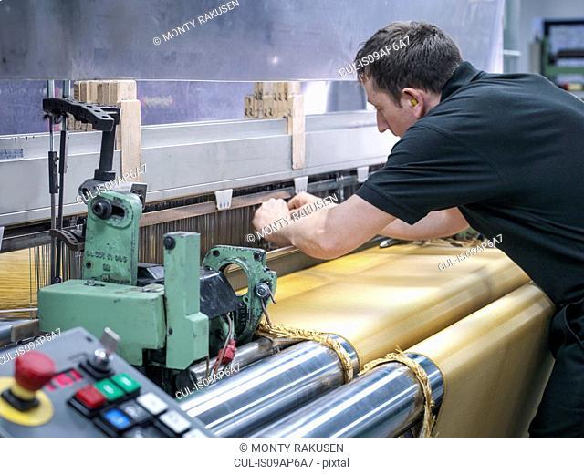 Worker weaving kevlar fabric in carbon fibre factory