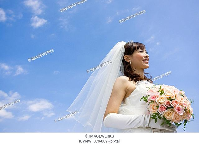 a smiling Japanese bride holding bouquet of flowers against blue sky