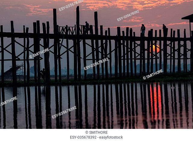 U bein wooden teck bridge with red sunset behind the structure, Amarapura, Myanmar (Burma)
