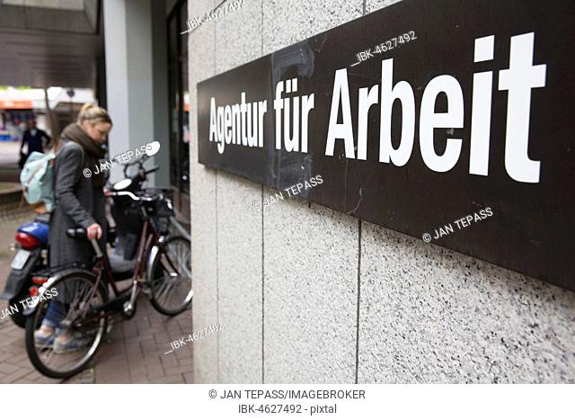 Young woman parks her bicycle in front of the Employment Agency, Cologne, North Rhine-Westphalia, Germany
