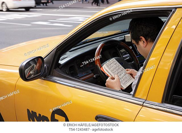 Cab driver reading a arabian book in New York City