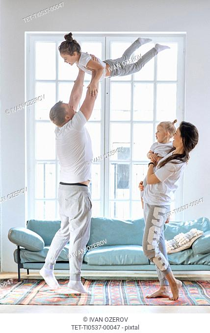 Parent lifting daughters by window