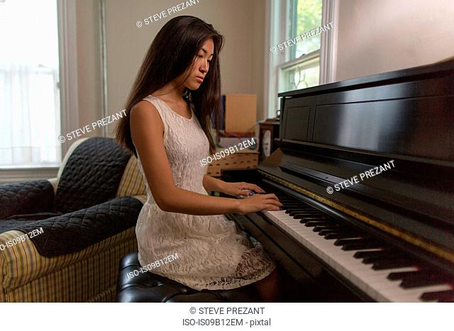 Teenage girl sitting playing piano in dining room