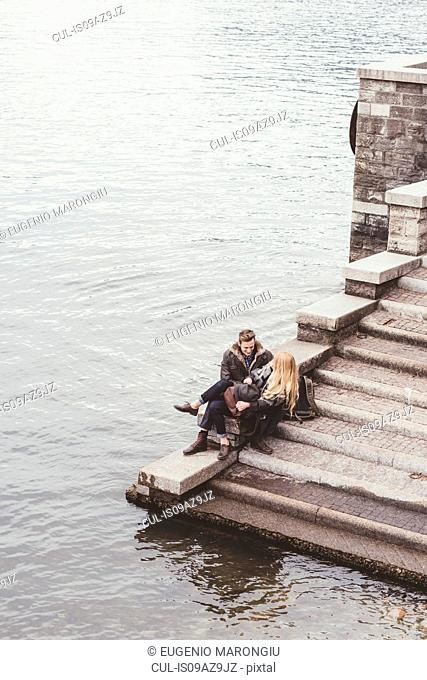 High angle view of young couple sitting on harbour stairs, Lake Como, Italy
