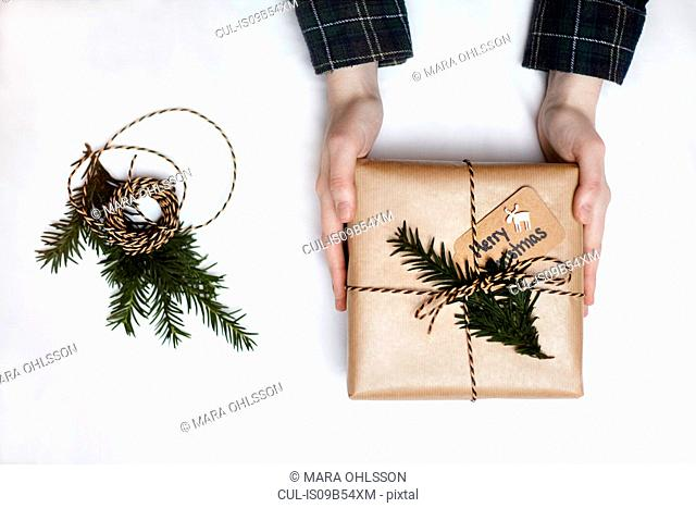 Woman holding Christmas gift wrapped in brown paper, decorated with fern and string, overhead view