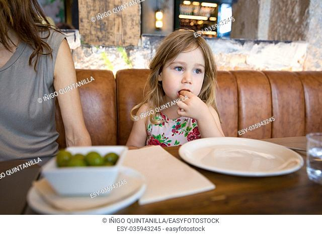Four years age blonde girl eating olive with hand next to woman mother sitting in brown leather sofa at restaurant