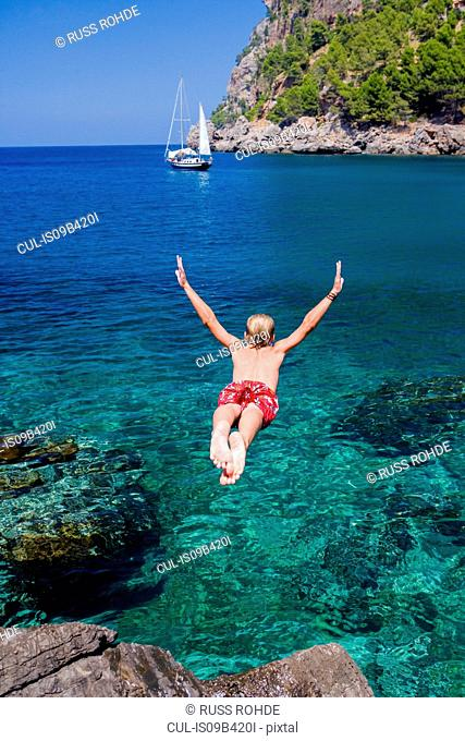 Rear view of young man diving into sea, Cala Tuent, Majorca, Spain