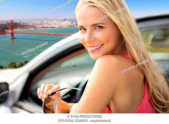 woman in convertible car over golden gate bridge