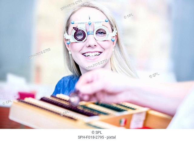 Portrait of cheerful young woman wearing trial frame in optometrist's shop, close-up