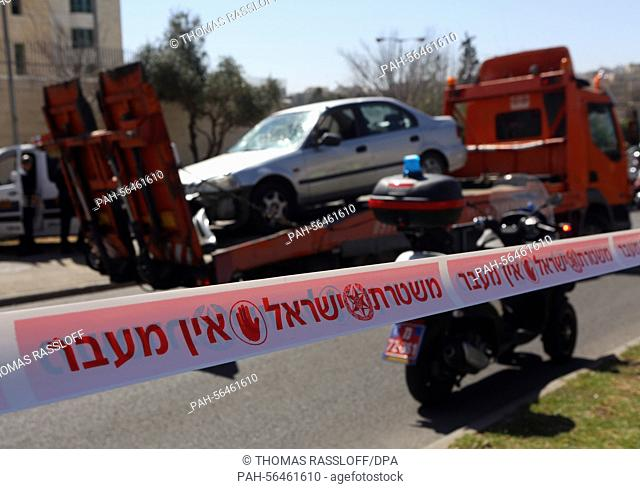 A truck carries a car wreckage off site on a street corner in Jerusalem, Israel, 6 March 2015. A car driver drove his vehicle into a group of waiting passengers...