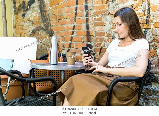 Woman using cell phone at an outdoor cafe