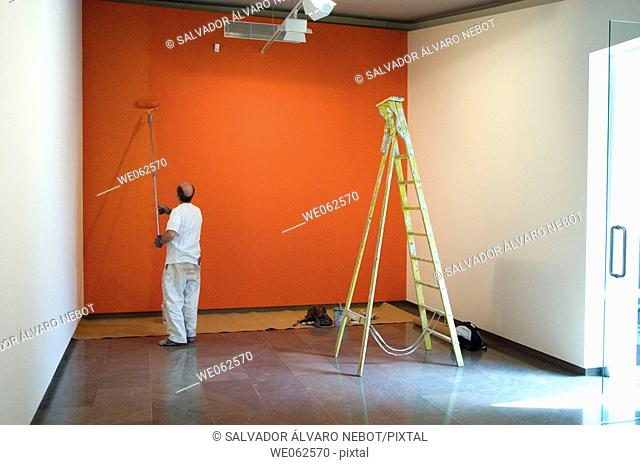 Man painting a wall in an exhibition hall