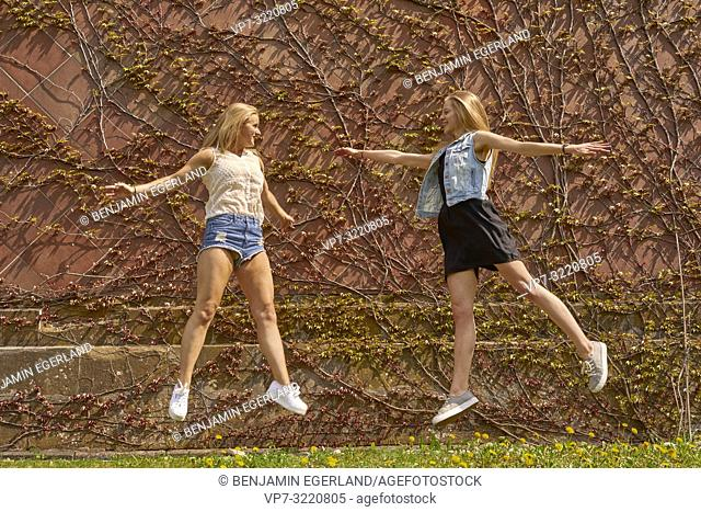 two women, jumping, friends, in Munich, Germany