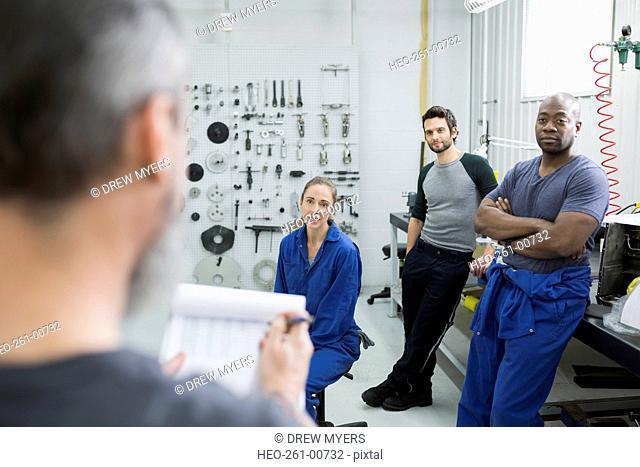 Helicopter mechanics in meeting in workshop