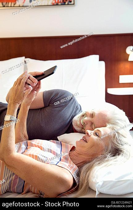 A couple lying on a bed looking at a mobile phone
