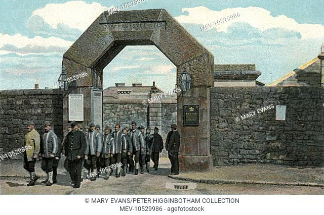 A group of prisoners and their guards pass through the main gate of Dartmoor Prison, Princetown