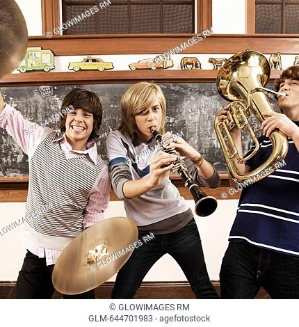 Three teenage boys playing musical instruments in a classroom