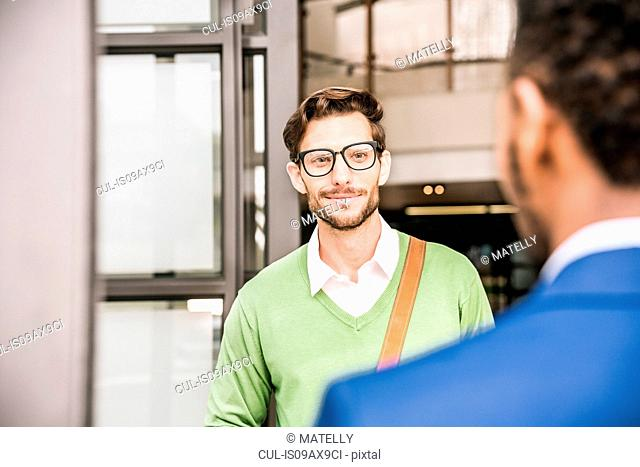 Over shoulder view of two businessmen meeting outside office building
