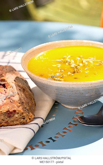 Bowl of hot carrot and ginger soup served with freshly baked bread. Colorful food