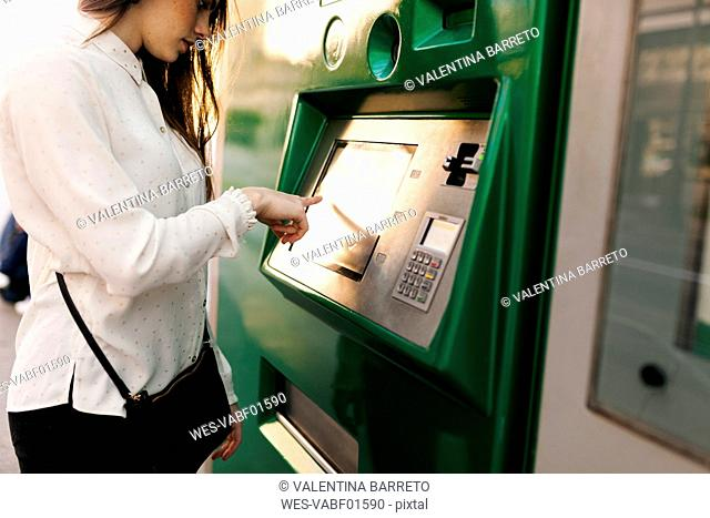 Spain, Barcelona, woman buying ticket from automated machine at station