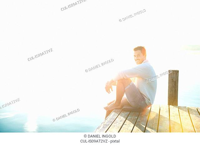 Portrait of happy young man sitting on pier of sunlit lake, Woerthsee, Bavaria, Germany