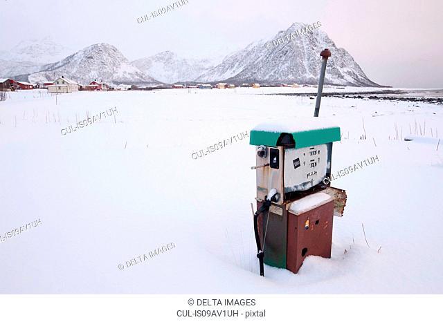 Old gas pump in snow covered landscape, Noss, Lofoten Islands, Norway