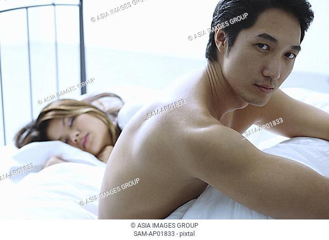 Man sitting on bed, woman asleep next to him