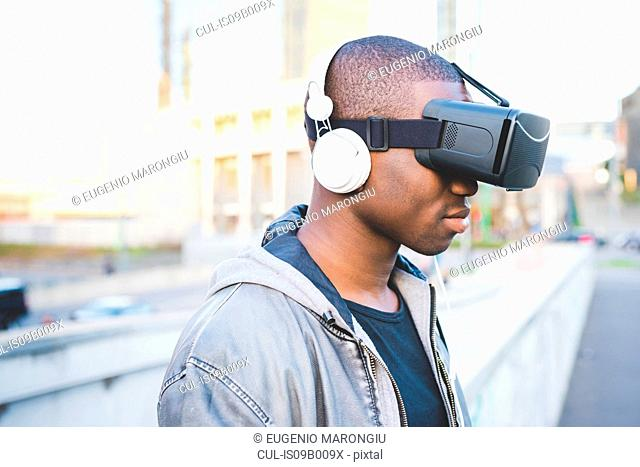 Young man outdoors, wearing virtual reality headset and headphones