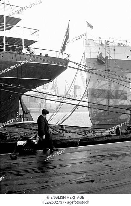 Ships berthed at the Royal Albert Dock, Canning Town, London, c1945-c1965. With a man pulling a lighter into the dockside for mooring