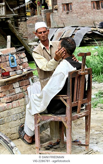 INDIA, LAWAYPORA, 24.06.2010, A roadside barber set up in the middle of a construction site messages a customer's face before giving him a shave