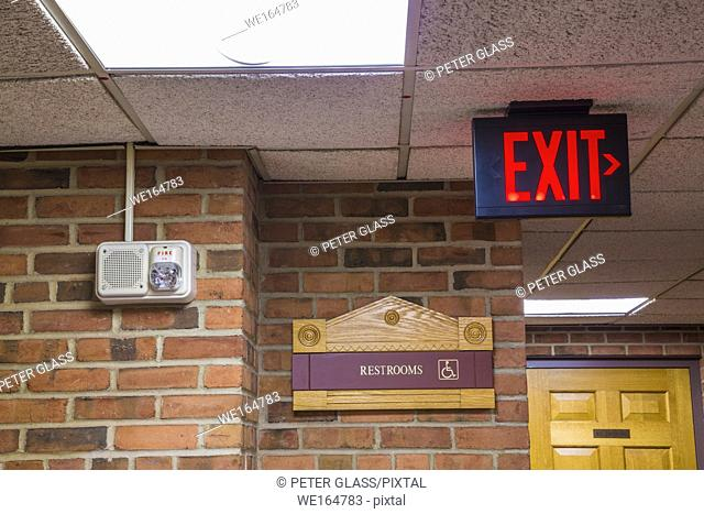 """""""""""""""Exit"""""""" and """"""""Restrooms"""""""" signs on brick walls in an office hallway"""
