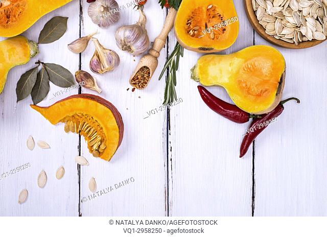 fresh pumpkin with seeds, garlic and spices on a white wooden background, empty space at the bottom