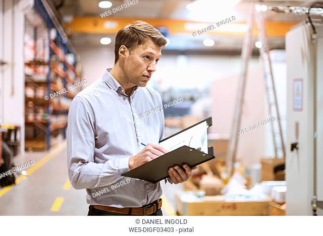 Businessman in factory holding folder
