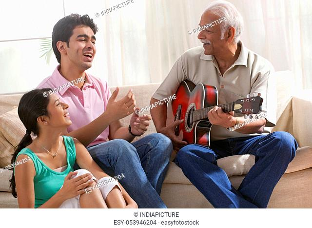 Grandfather playing the guitar and grandchildren singing