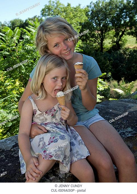 Sisters sitting in garden eating ice cream