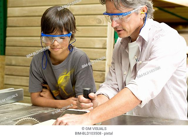 Hispanic father and son in workshop