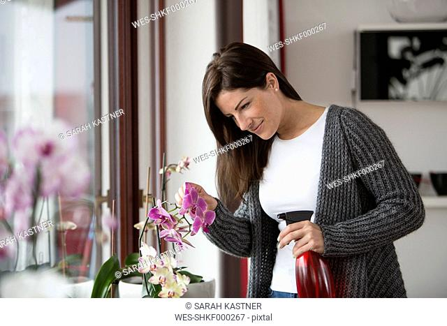 Woman with spray bottle watching orchid