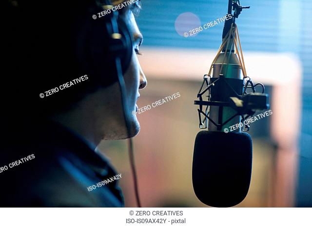 Male musician in recording studio, singing into microphone