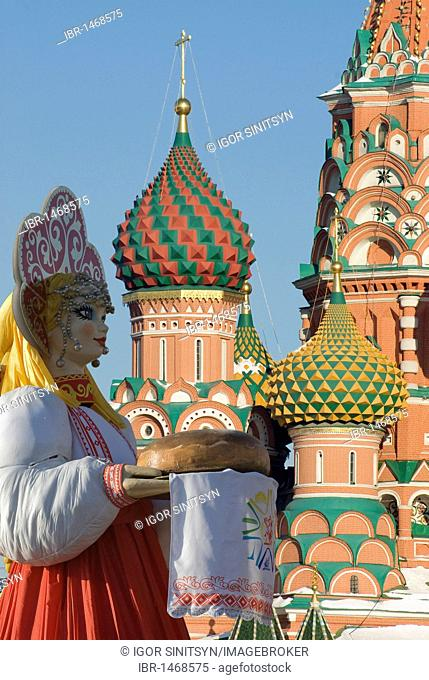 Russian doll in front of the towers of the orthodox Saint Basil's Cathedral, Moscow, Russia