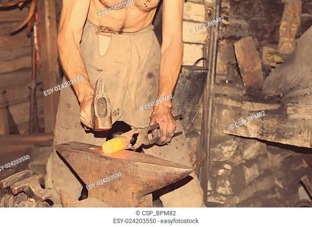 Blacksmith working metal with hammer