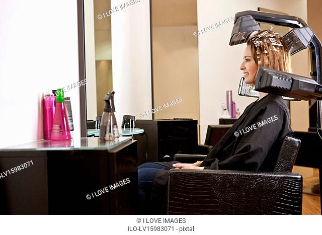 A female client looking at herself in a mirror in a hairdressing salon