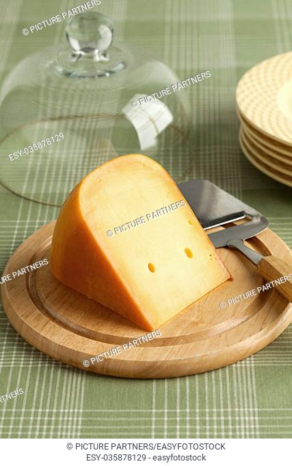 Piece of Dutch Gouda cheese on a wooden board at breakfast