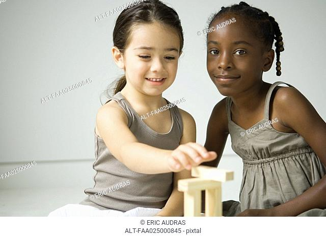 Two girls sitting, playing with blocks, one smiling at camera
