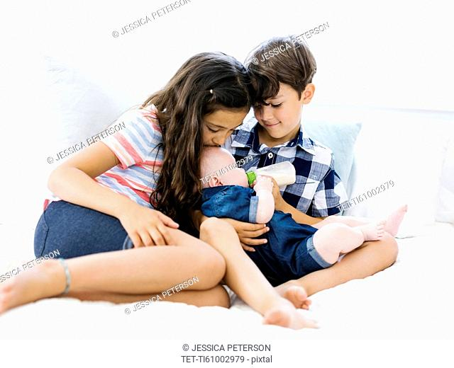 Three siblings (6-11 months, 6-7, 10-11) sitting together on bed